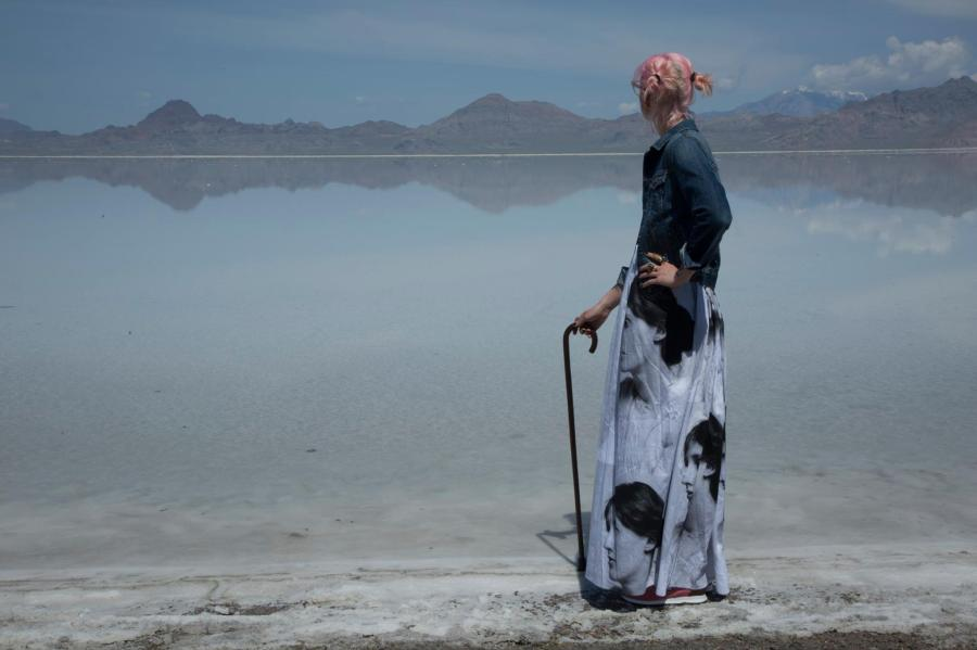Karrie stands on shoreline of flooded salt flats. Wearing a skirt printed with the portrait of Virginia Wolf and holding a wooden kane, Karrie looks pensively towards the mountains on the horizon. Soft clouds float in the distance in the upper right of the photograph.